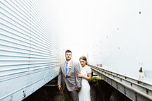 bride and groom standing between trucks