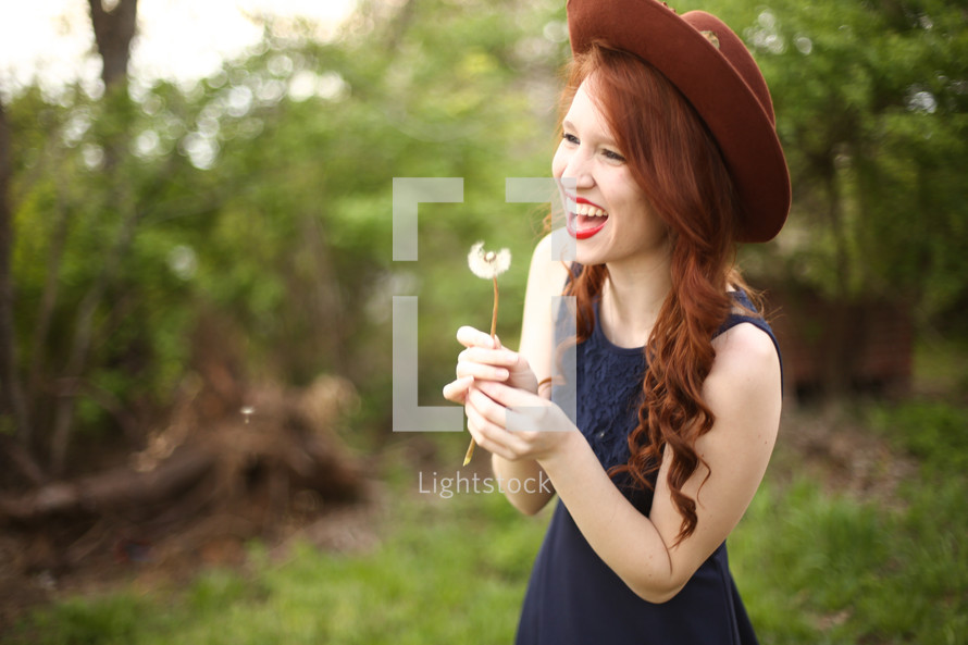 a woman blowing a dandelion outdoors