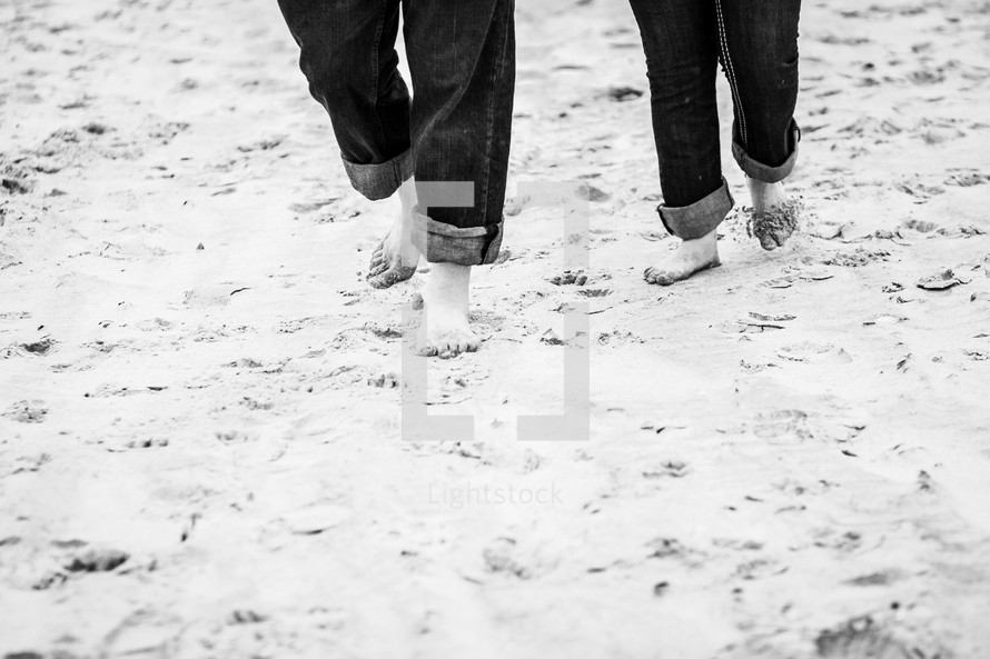 a couple with rolled up jeans walking through the sand