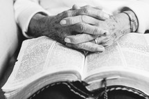 An elderly woman's hands folded on an open Bible.