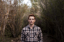 young man with red hair standing outdoors in a plaid shirt