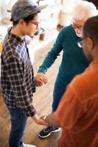 men holding hands in prayer