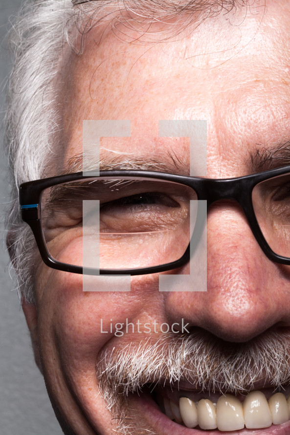 The face of a smiling man in glasses.