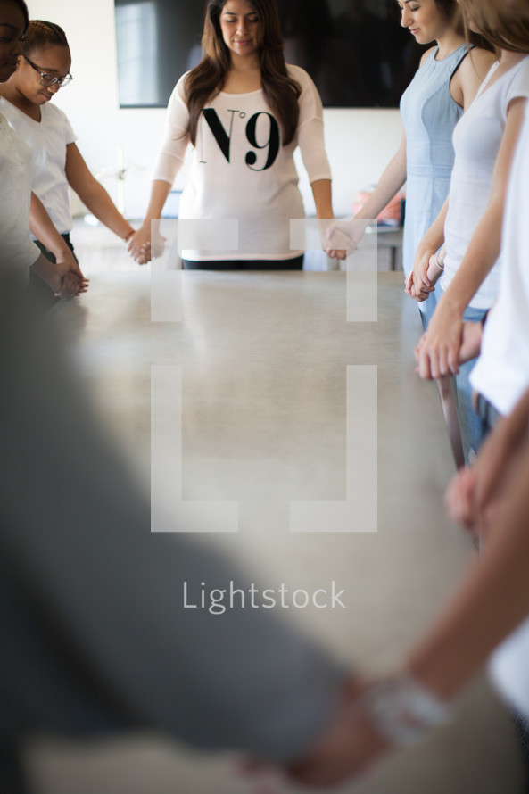 holding hands praying around a table