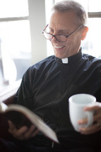 A smiling minister reading the Bible and holding a cup of coffee.