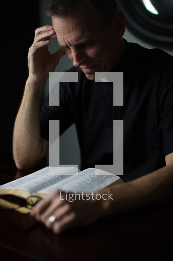 A priest reading a Bible