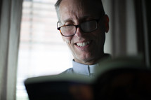 A smiling minister reading the Bible.