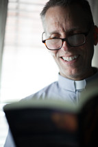 A smiling minister wearing a clerical collar reads the Bible.