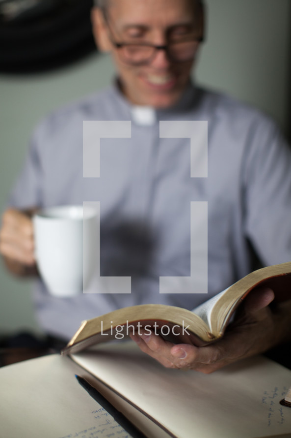 A smiling minister reading the Bible and drinking coffee.