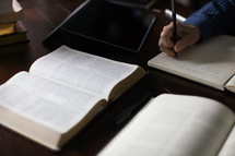 A man's hand takes notes at a desk upon which is an open Bible.