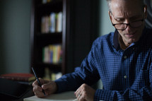 A man in glasses takes notes at a desk.