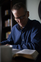 A middle-aged man sits at a desk studying the Bible.