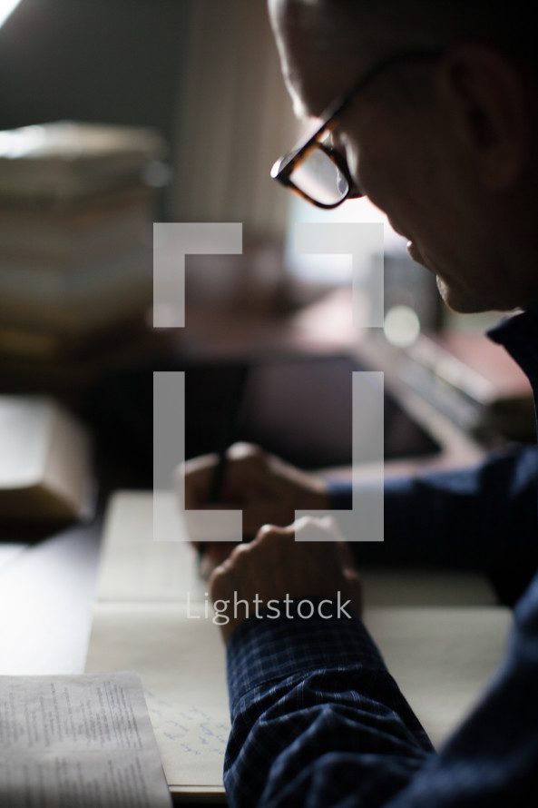 A man taking notes at a desk.