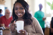 woman holding a coffee mug at a small group gathering