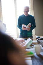 A man standing at a table leading a small group in a Bible study.