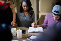 A small group praying around a table.