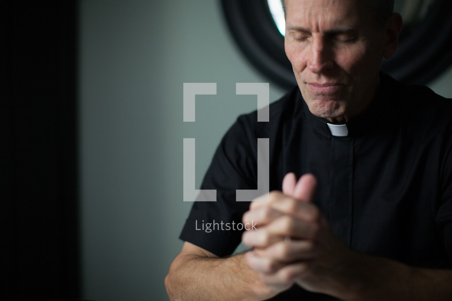 A minister wearing clerical clothes clasps his hands and closes his eyes in prayer.