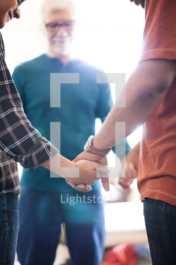 A small group of men holding hands in a prayer circle.
