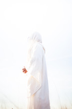 A Biblical character in white clothes with hands clasped against a white background.