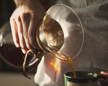 a man pouring coffee from a pour over dripper