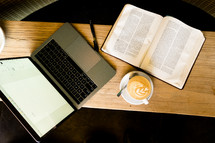 a laptop computer, open Bible, and latte on a coffee table