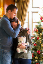 couple hugging and a teddy bear in front of a Christmas tree