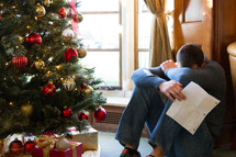 sad man sitting near a Christmas tree