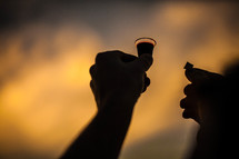 hands holding up the bread and wine for communion in praise and worship to God