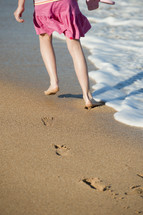 girl child walking leaving footprints in the sand on a beach