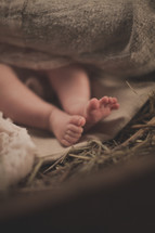 The feet of baby Jesus in the manger.