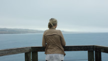a woman looking over a railing at the ocean