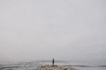 woman standing on a jetty looking at the ocean