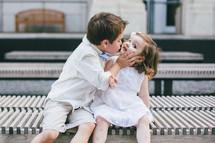 a little boy kissing a little girl