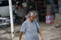 woman walking on a dirt street in Indonesia