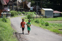 children walking on a street in Toraja