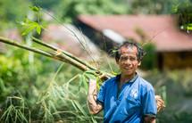 man carrying bamboo