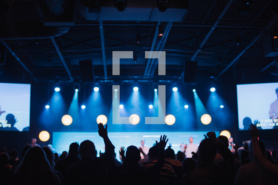 audience with raised hands at a contemporary worship service