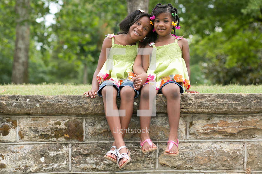 sisters sitting on a rock wall