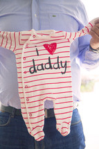 father holding an infant's clothes - l love daddy