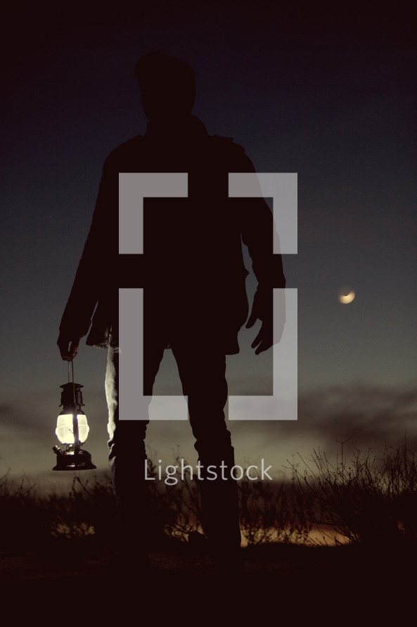 a man holding a lantern outdoors at night