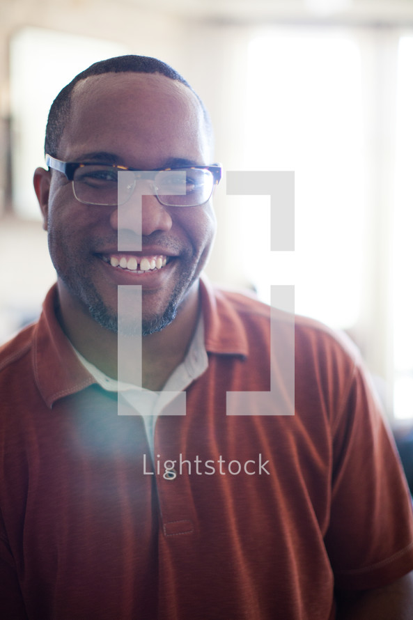 A smiling man wearing glasses.
