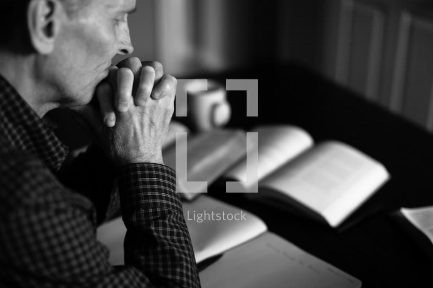 A minister prays as he prepares a sermon.