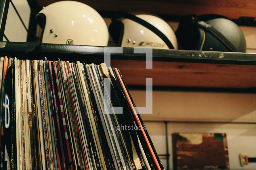 records and helmets on a bookshelf