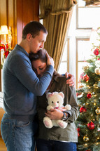 couple hugging in front of a Christmas tree, Christmas sadness