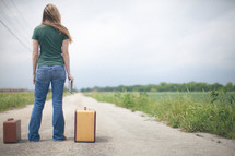 Woman standing in the middle of a dirt road with her luggage and a bible in her hand.