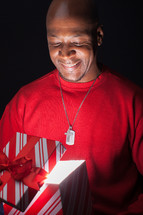 African American man looking happily into a gift box full of light.