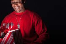 African American man looking happily into a Christmas gift box full of light.