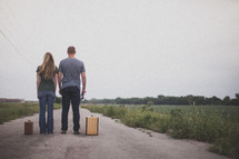 man and woman standing with suitcases looking down a long open road