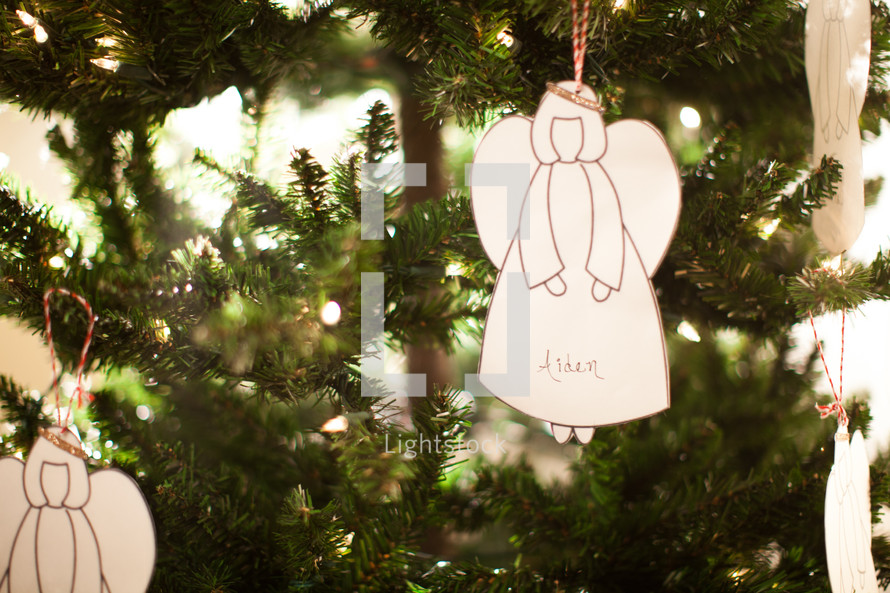 a white angel ornament hanging on a Christmas tree