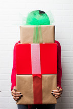 a woman holding wrapped gifts towering over her head